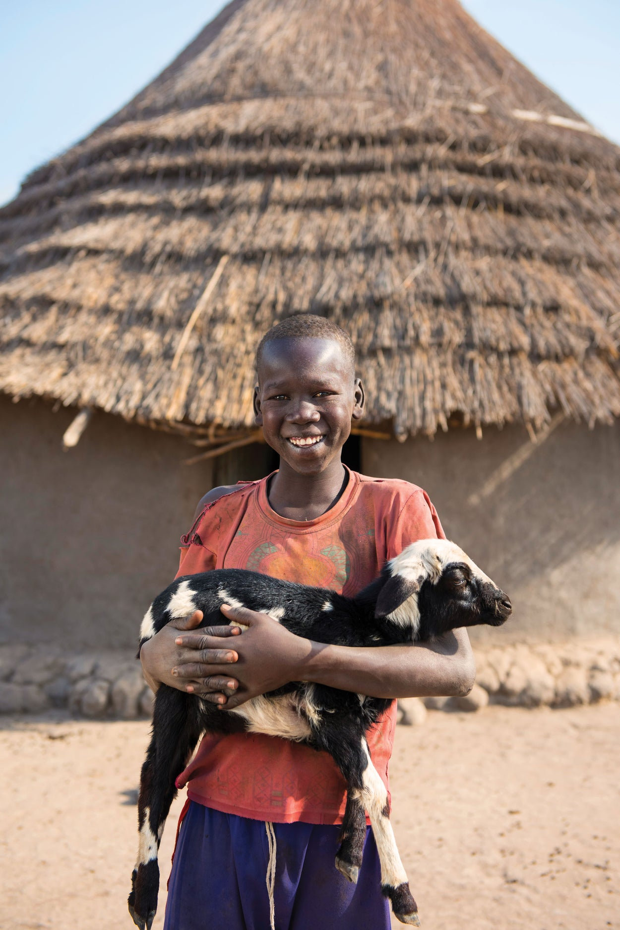 A boy in South Sudan holds a goat.