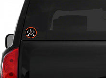 An orange circle around white CLE crossed fishing rods sticker on the back of a black truck.