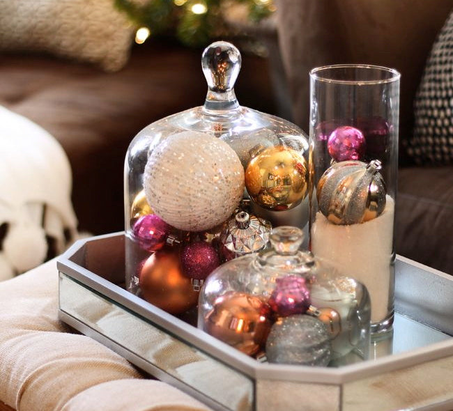One of the easiest ways to add a touch of holiday magic is simply by placing ornaments in cloches, a bowl or other visually stimulating vessel.  Place them on a coffee table, mantle, or shelves for that unexpected pop of color!  Photo Credit The Hunted Interior.