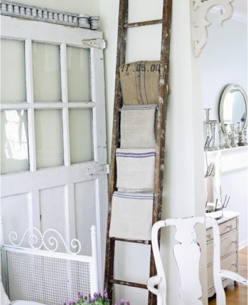Why not use a ladder as a towel rack. In this shabby-chic version, the ladder adds a farmhouse feeling to the room.