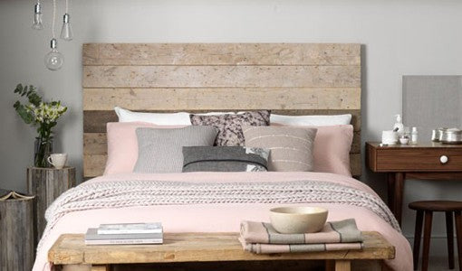 This bedroom receives a fresh look with the whitewashed-boards used for a headboard along with logs as a place for fresh flowers and a book. What a clever way to turn an ordinary bedside table into something extraordinary. Photo found on Pinterest.