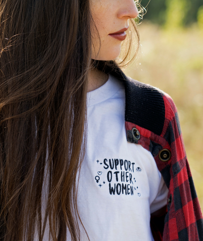 "Unisex white t-shirt with ""support other women"" embroidered logo on the chest"