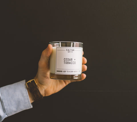 Hand holding Cedar and Tobacco Soy Candle