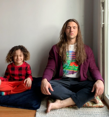 Father and son meditating, sitting side-by-side with legs crossed.