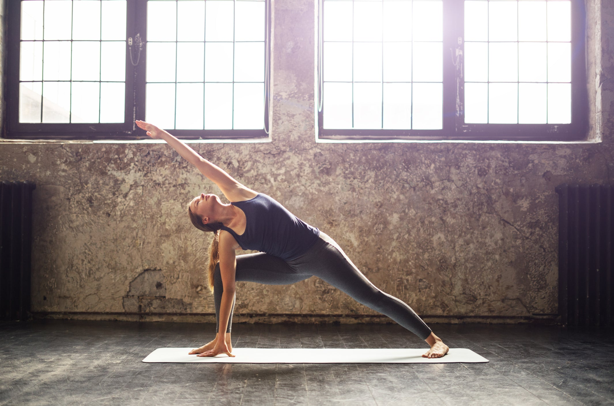Woman holding a yoga pose in a naturally lit studio