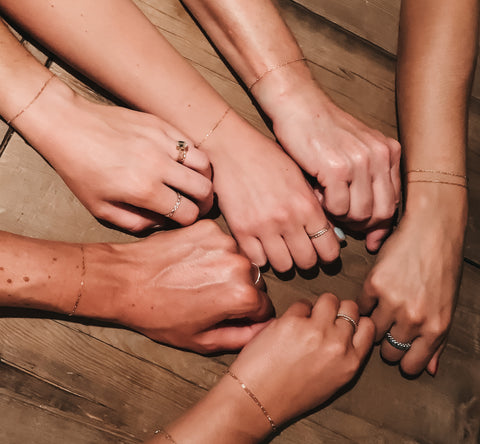 hands in a circle all wearing matching delicate chain bracelets