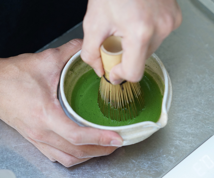 Woman whisking matcha with chasen whisk