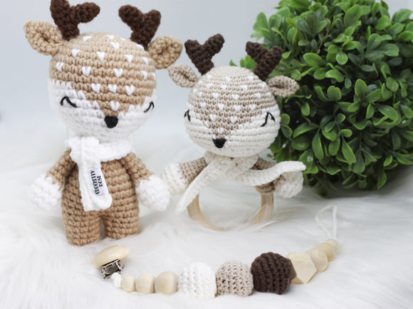 Crocheted stuffed toy reindeer in beige and white with crocheted deer rattle toy and pacifier clip made with natural wood balls, crocheted balls in brown, beige and white colours.