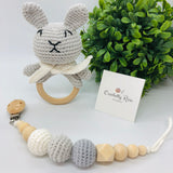Baby rattle in a bunny design (grey and white colours) with a 70 millimetres natural wood ring as a handle in a set with a pacifier dummy clip made with natural wood & crocheted beads in a baby cotton yarn white cord