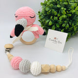 Baby rattle in a flamingo design (pink, grey and white colours) with a 70 millimetres natural wood ring as a handle in a set with a pacifier dummy clip made with natural wood & crocheted beads in a baby cotton yarn white cord