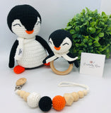 Crocheted stuffed toy penguin in black and white with crocheted penguin rattle toy and pacifier clip made with natural wood balls, crocheted balls in orange, black and white colours.