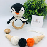 Baby rattle in a penguin design (black, orange and white colours) with a 70 millimetres natural wood ring as a handle in a set with a pacifier dummy clip made with natural wood & crocheted beads in a baby cotton yarn white cord