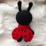 One 7 inch ladybug stuffed toy with red scarf. Back looking.