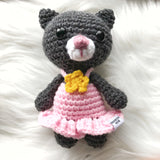 One 7 inch dark grey cat stuffed toy with pink dress and yellow flower on dress.