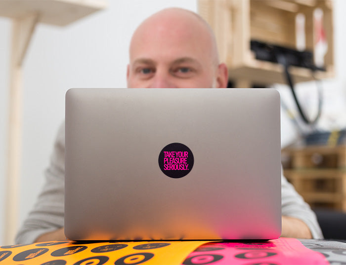 tabtag artis partisan behind a macbook with a neon decal on it