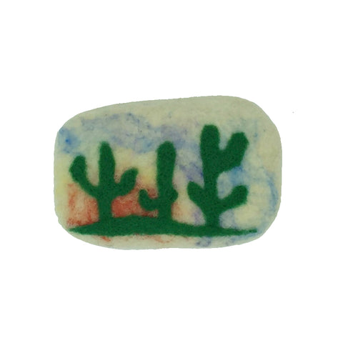 Bar of soap covered in wool with cactus against sunrise.