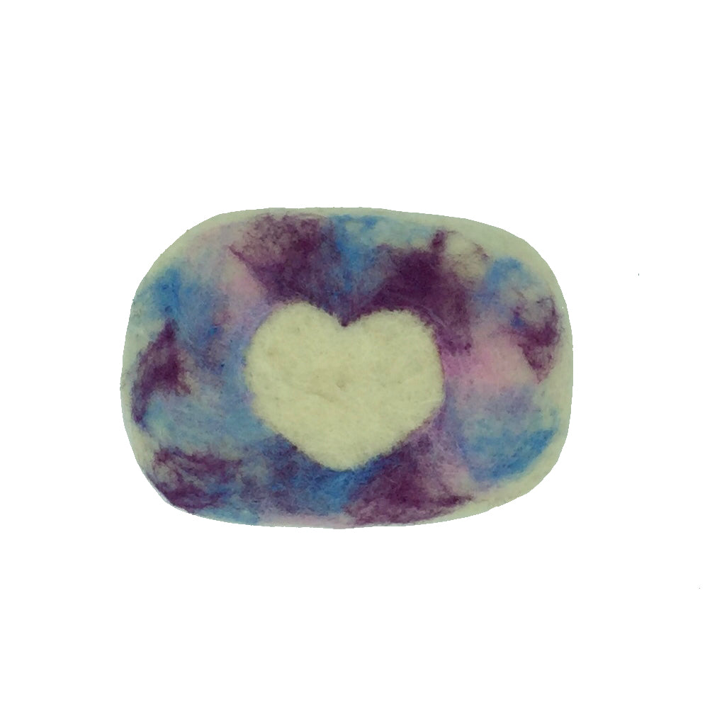 Oval bar of soap covered on wool with a white hear in the center surrounded by a background of blues, pinks and purples.