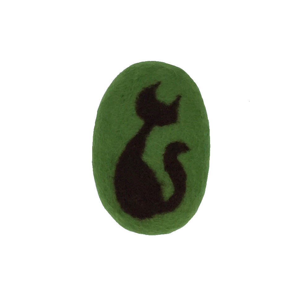 Oval bar of soap covered in wool with a sitting cat, background in green.