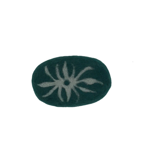 Oval bar of soap covered with green wool with a white star like design.