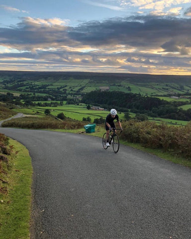 A cyclist in black climbs a country lane with a view over the valley in the background.