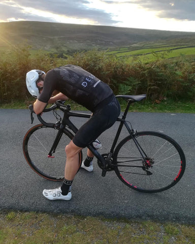 A cyclist in black recovers from an effort with a country view in the background
