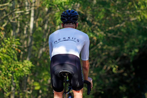 A cyclist descends into a wooded lane wearing a white Dessus Aero Jersey and Pro Bib Shorts.