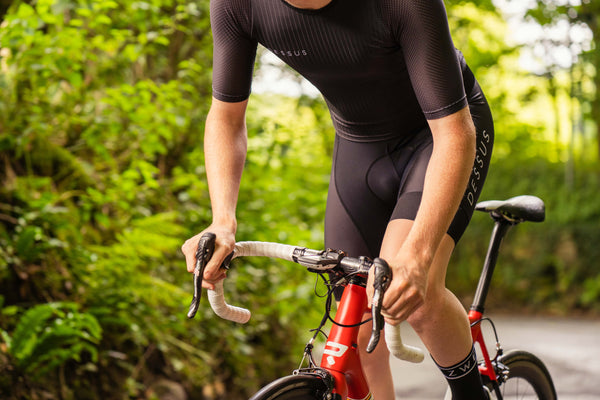 A cyclist climbs a wooded country lane in a Dessus Aero Jersey and Pro Bib Shorts. The Dessus Aero Jersey is a zipless cycling jersey with integrated rear pockets, it can be customised to your design.