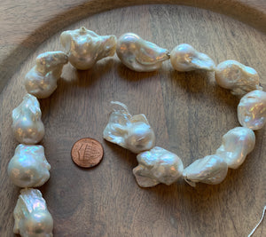 Photo is of a strand of large, white, baroque pearls on a wood background with a US penny for scale