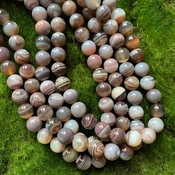 10mm smooth round Botswana agate bead strands on green background