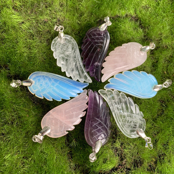 carved amethyst wing pendant, carved rose quartz wing pendant, carved opalite wing pendant, carved quartz wing pendant on green background