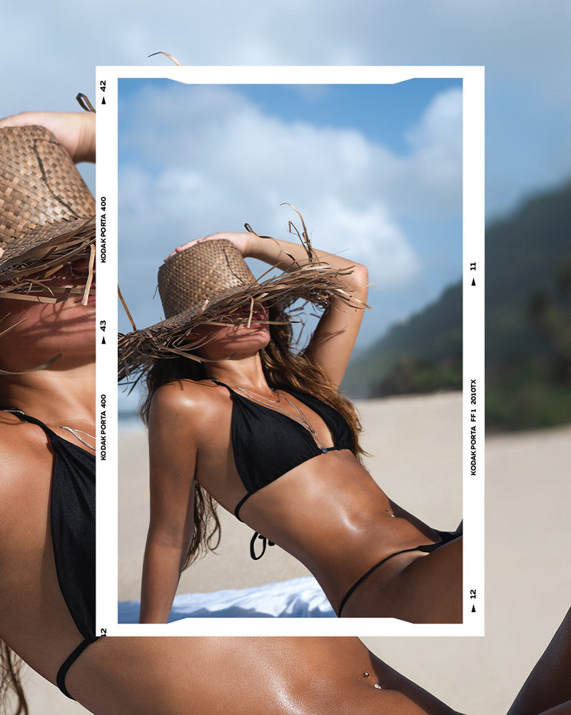 Girl in black bikini wearing straw hat at the beach