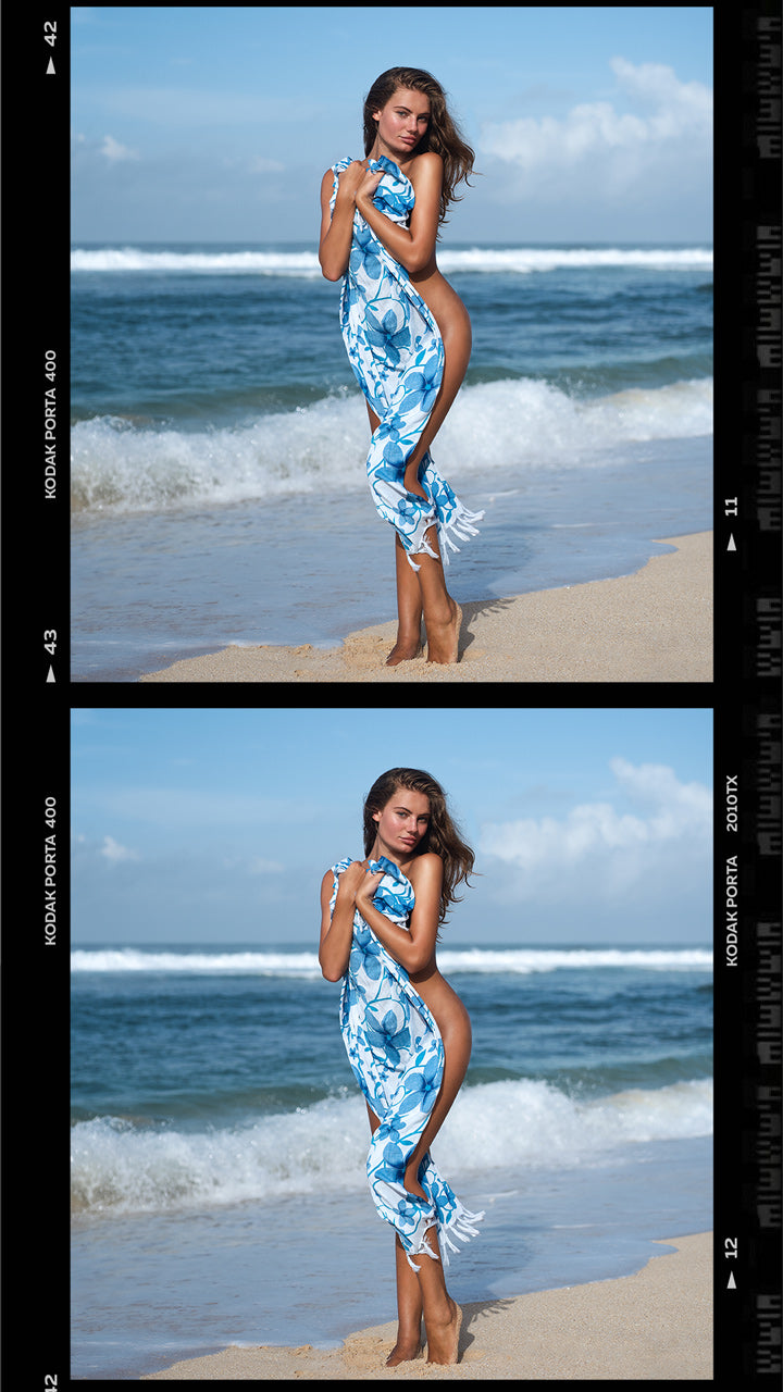 Model covering her body with a blue towel standing by the beach shore