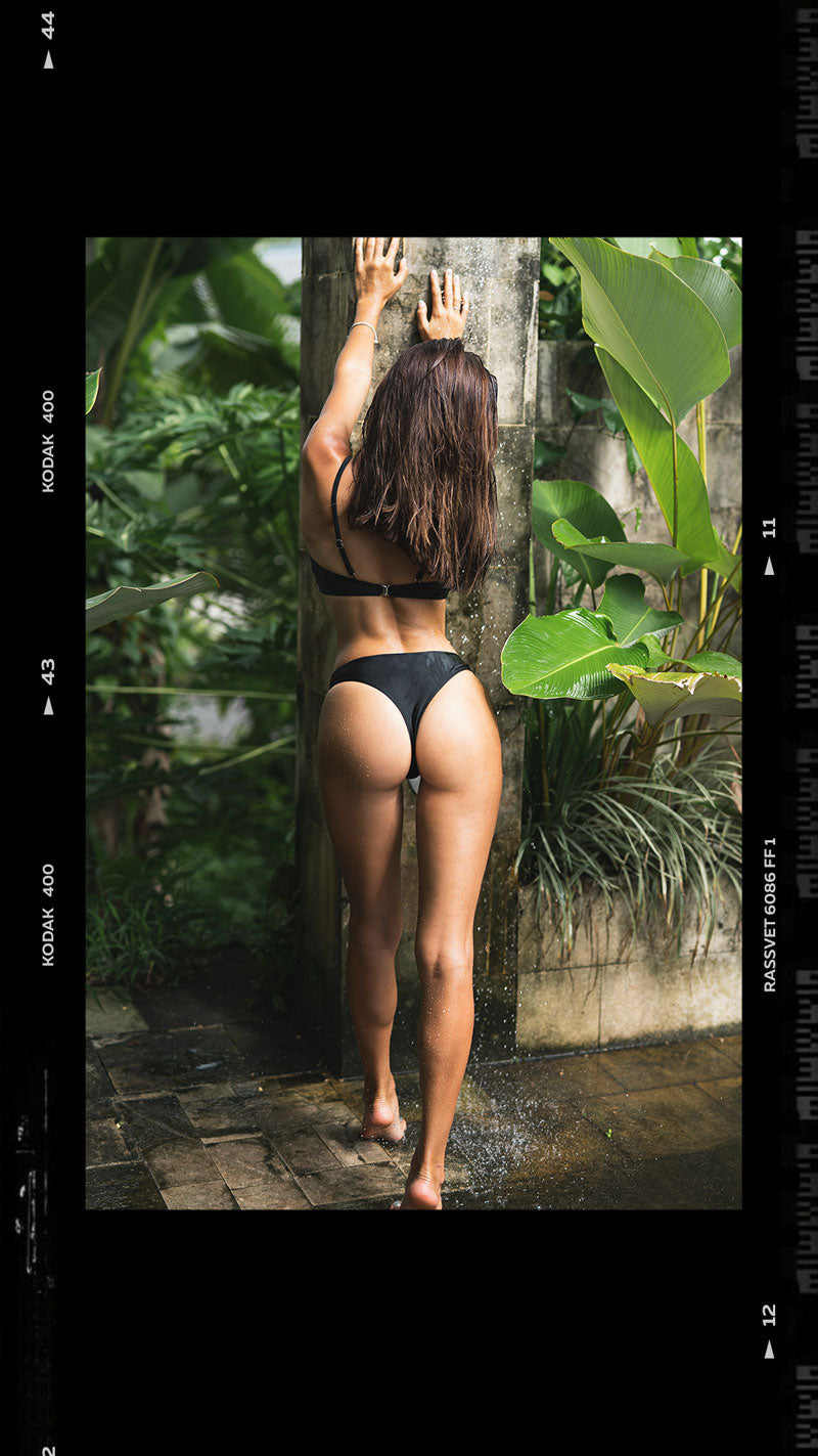 female model wearing black bikini posing in tropical outdoor villa in Bali