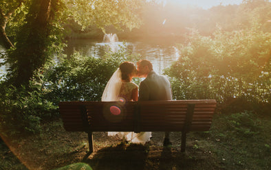 Couple kissing on a bench on their wedding day
