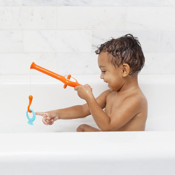 Young child enjoying bath play with the Boon Cast bath toy