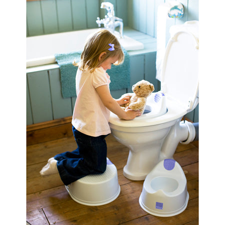Girl using the MioStep stool on the toilet