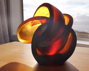 Abstract geometric cast glass sculpture of the atom by Stephen Williams.