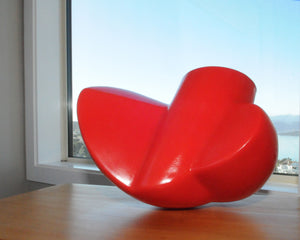 Twist - Red plastic lamp sculpture in daylight by Stephen Williams