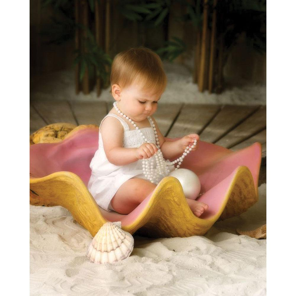 baby sitting inside large clam shell prop
