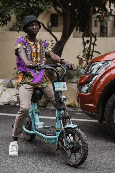 A man wearing a Dashiki on his scooter