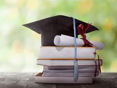 graduation hat with degree on top of books