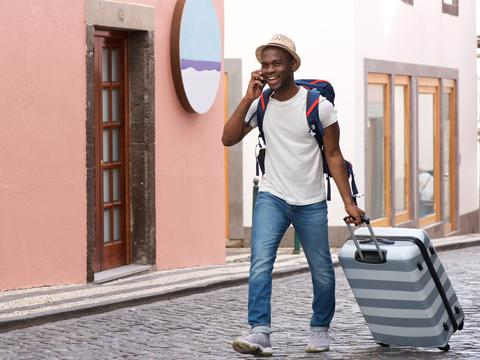 man talking on cell phone with a suitcase