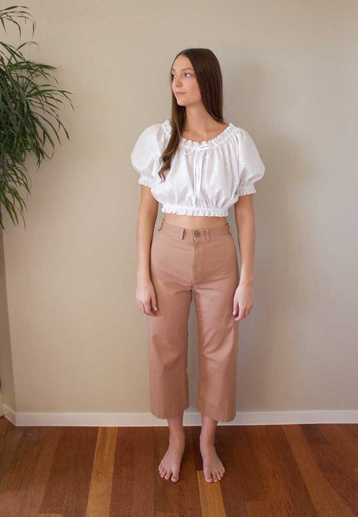 The Polly Top is the cutest top you need this summer. A fun and feminine cotton emboidery anglaise fabric with plain cotton casings with elastic and a roll hem finish on all edges. The garment is perfectly finished with a grosgrain ribbon bow. This cropped top can be worn on or off the shoulders.