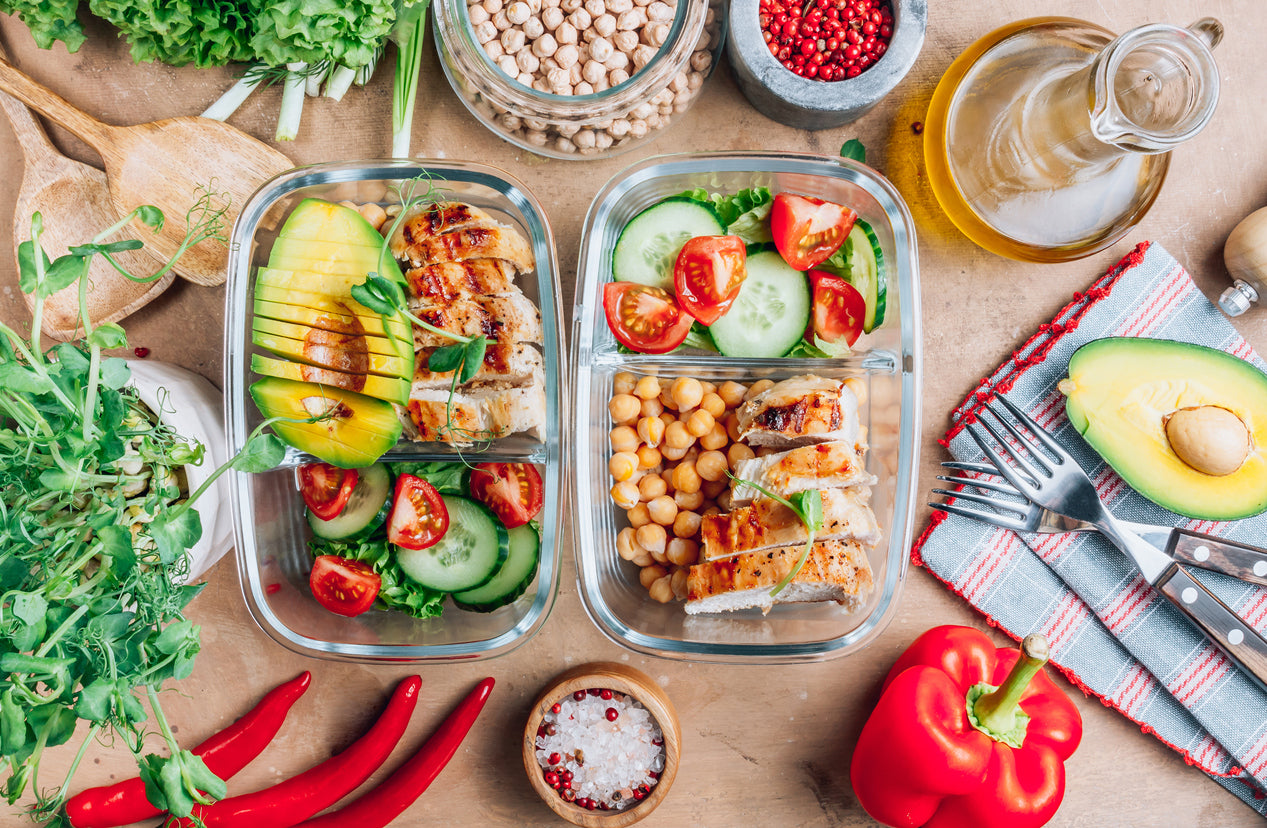 A pair of lunch boxes packed with healthy snacks, including chickpeas, cucumbers, tomatoes and avocado. Other veggies surround the lunch boxes.