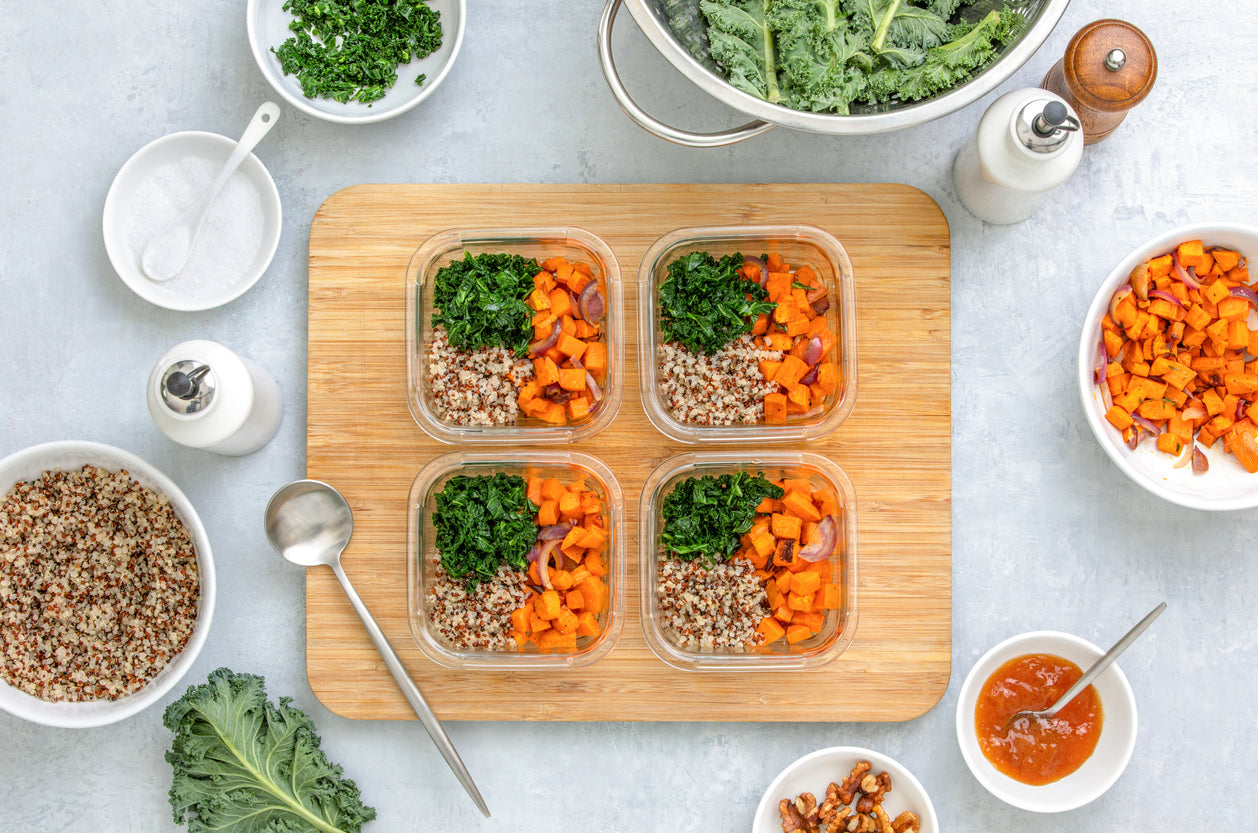 Four meal prep containers filled with food on a cutting board.