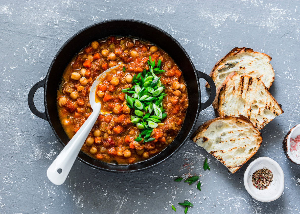 Chili with chickpeas, tomatoes, ground beef, and celery topped with green onion. Baguette slices placed next to the skillet for dipping