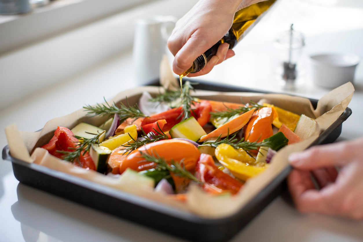 Olive oil being drizzled over a baking sheet full of vegetables
