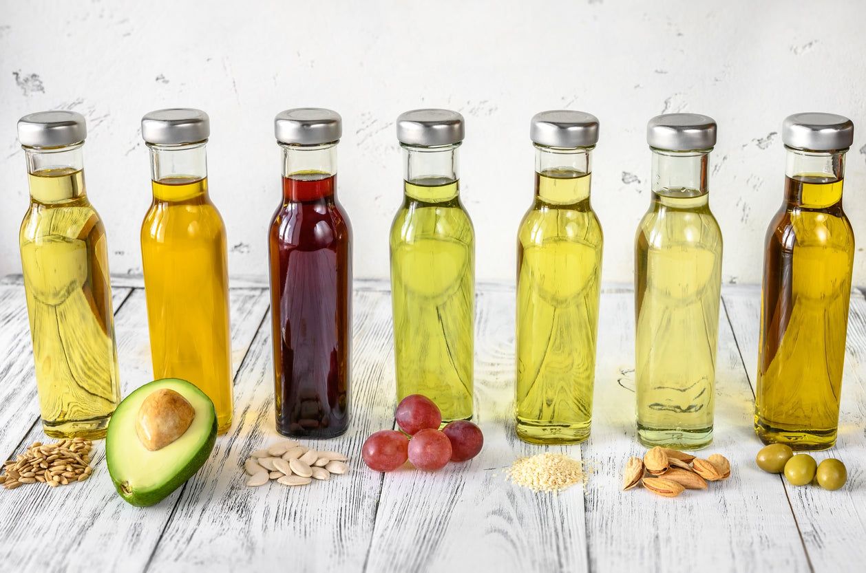A variety of different oils lined up on a countertop.