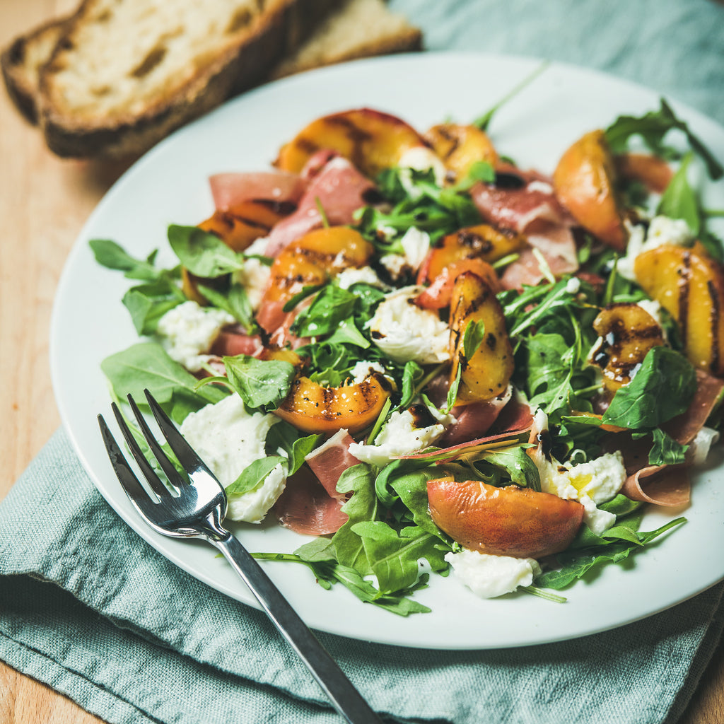 Grilled peaches topped on a salad with fresh cheese and prosciutto and a spicy fig dressing