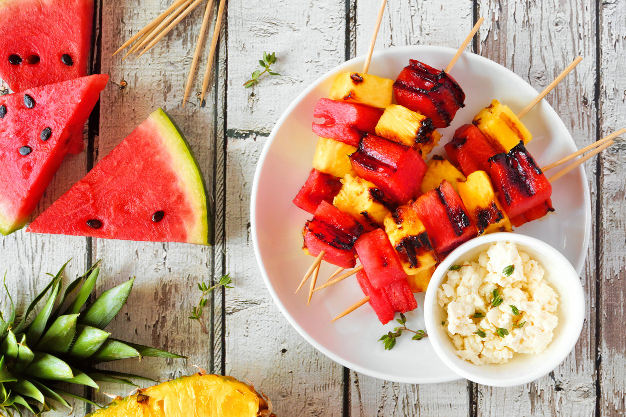 Watermelon and pineapple skewers with grill marks on a plate, with a size of feta cheese.